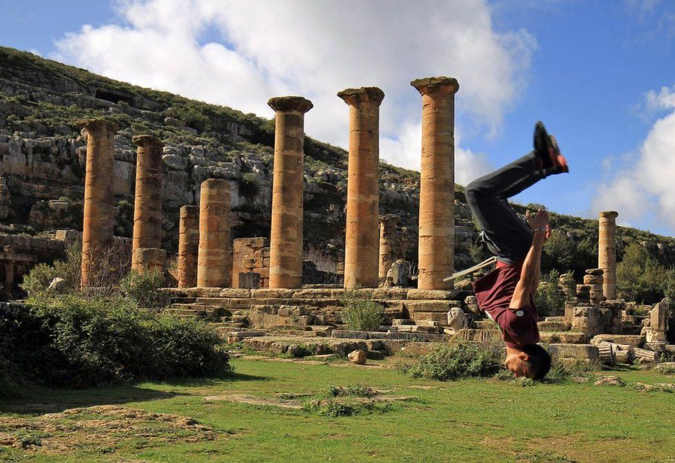 A man jumps acrobatically next to a row of columns.