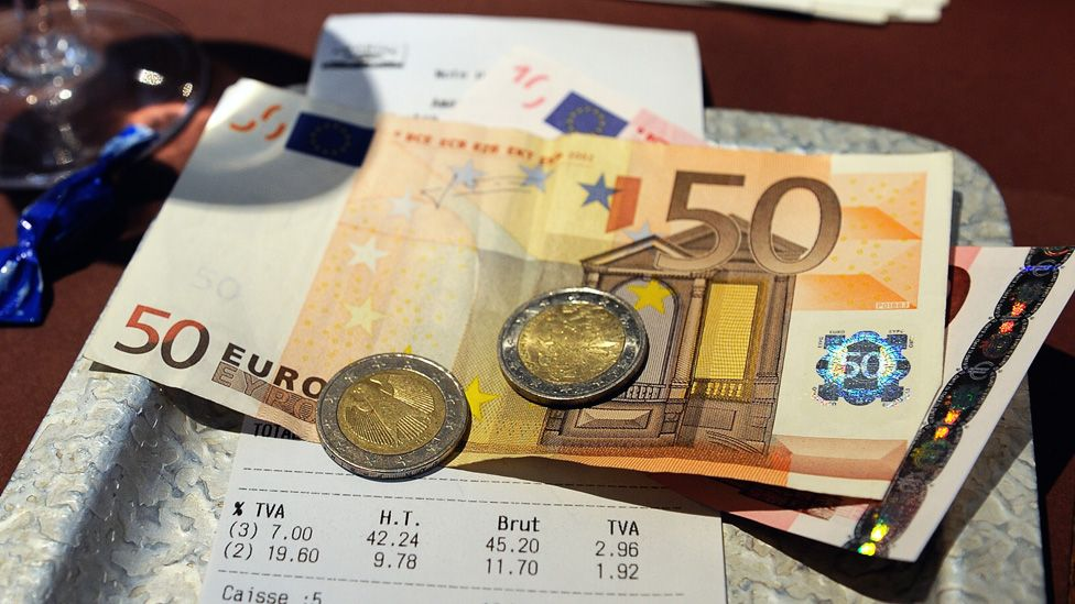 Euro notes and coins on a restaurant table, paying a bill.