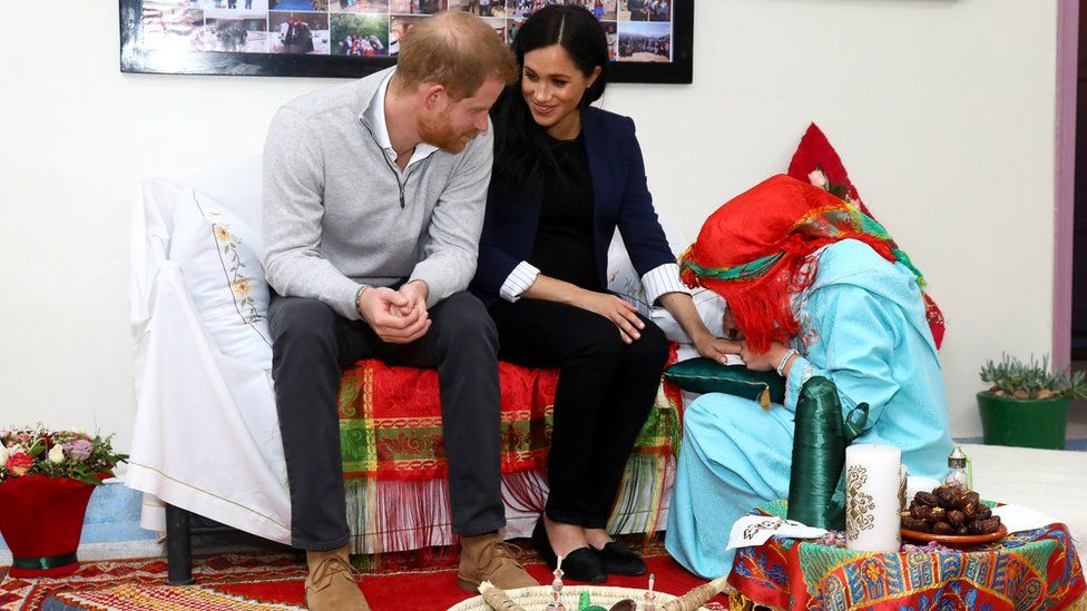 The Duchess of Sussex sits with Prince Harry as henna is applied to her hand