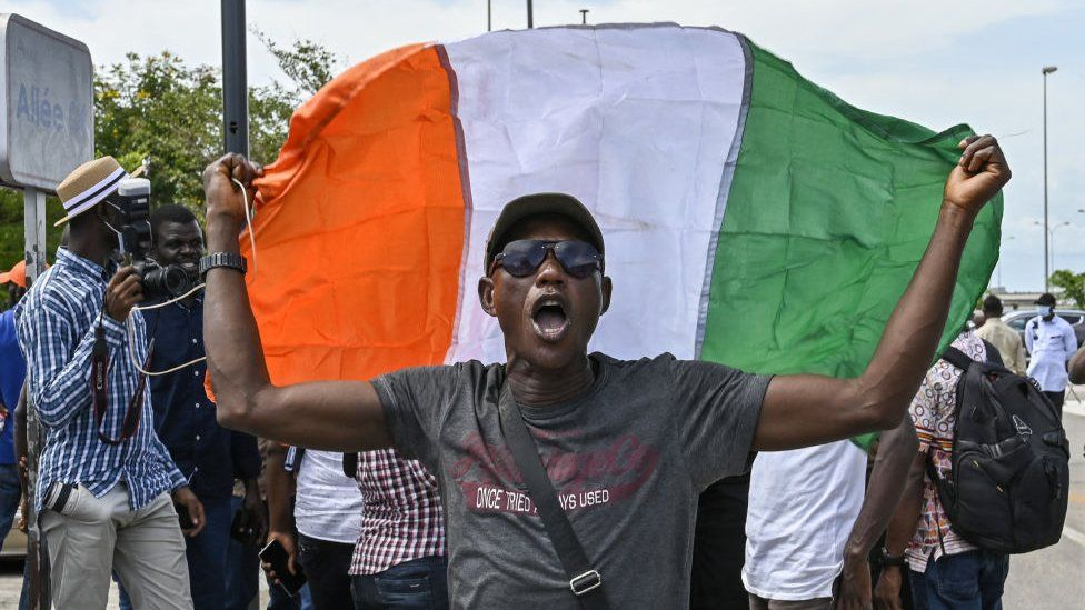 A man holds an Ivorian flag during a welcoming ceremony for several supporters of Ivorian former president Laurent Gbagbo upon their arrival in Abidjan at the end of ten years of exile in Ghana