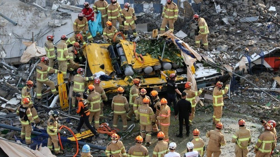 South Korean firefighters search for passengers from a bus trapped by the debris of a collapsed building in Gwangju