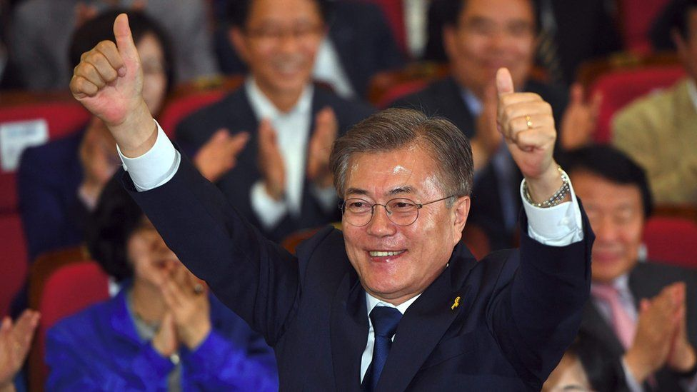 South Korean presidential candidate Moon Jae-in (C) of the Democratic Party reacts as he watches screens showing the result of exit polls of the presidential election at a hall of the National Assembly in Seoul on May 9, 2017.