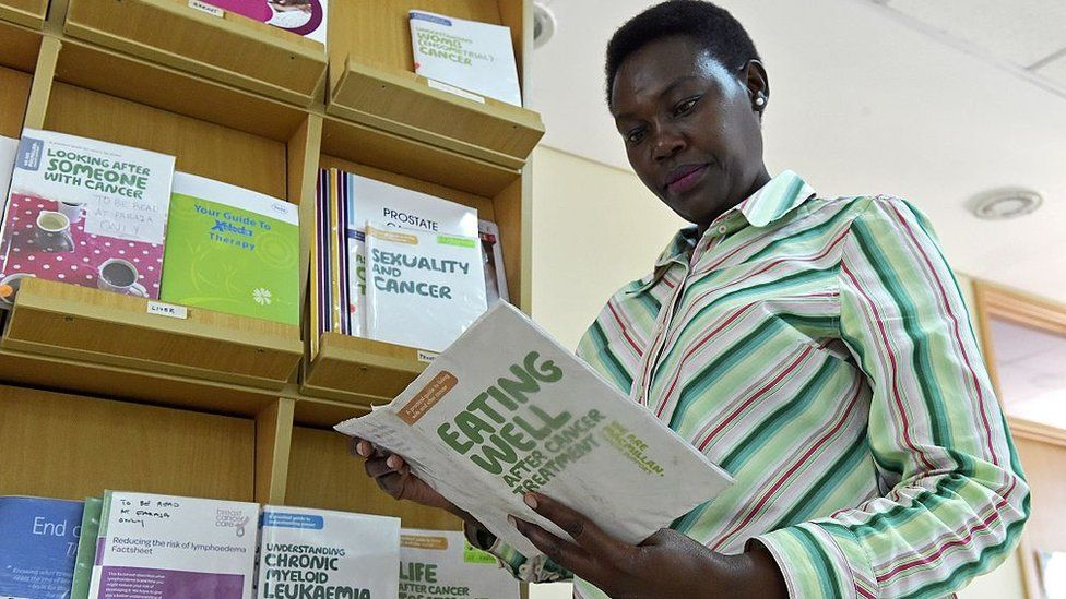 Kenyan school teacher and breast cancer survivor Rose Kariuki reads pamphlets at the Faraja cancer care centre in Nairobi on December 19, 2016