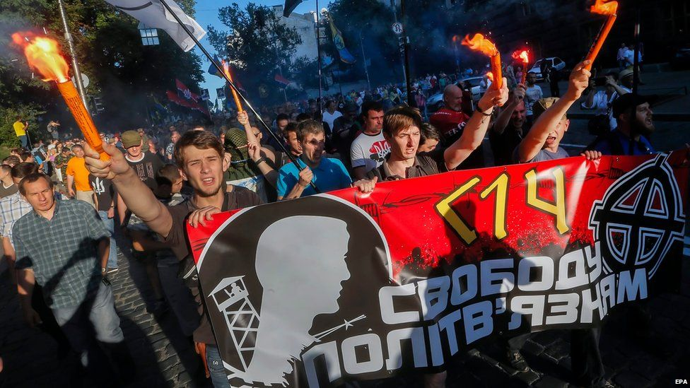 """Members and supporters of Right Sector and other ultra-right political parties burn torches and carry a poster with the slogan """"Freedom to political prisoners"""" as they march during a protest in Kiev, Ukraine, 3 July 2015"""