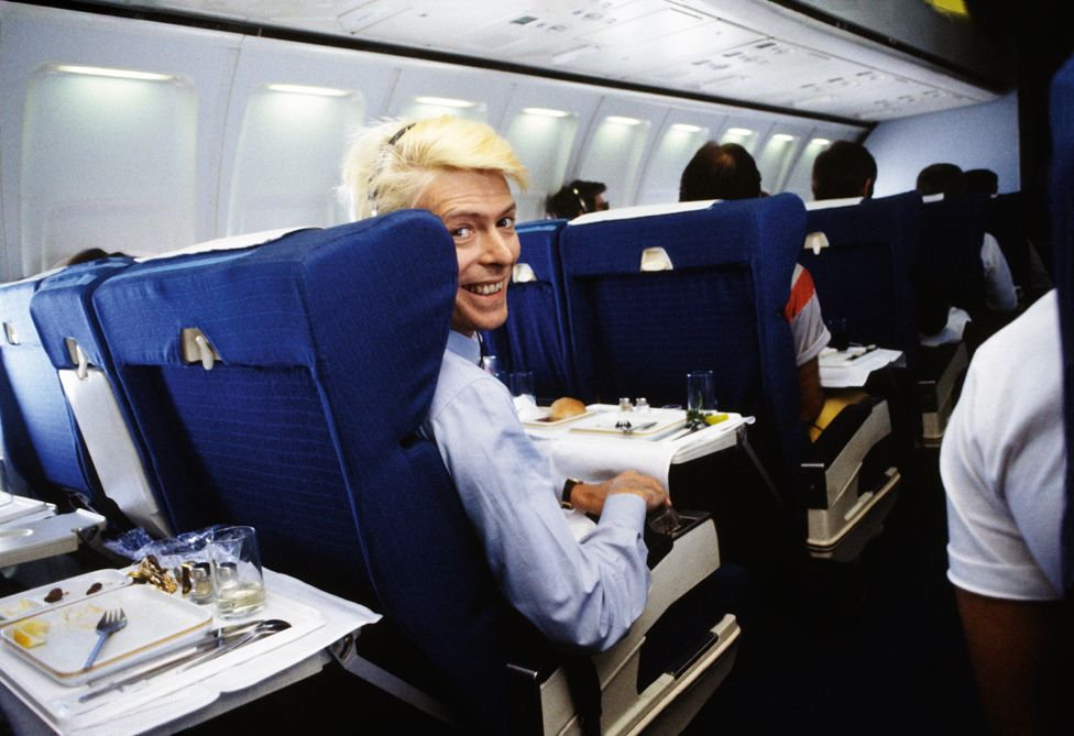 David Bowie on a commercial flight during the Australian leg of his Serious Moonlight tour.