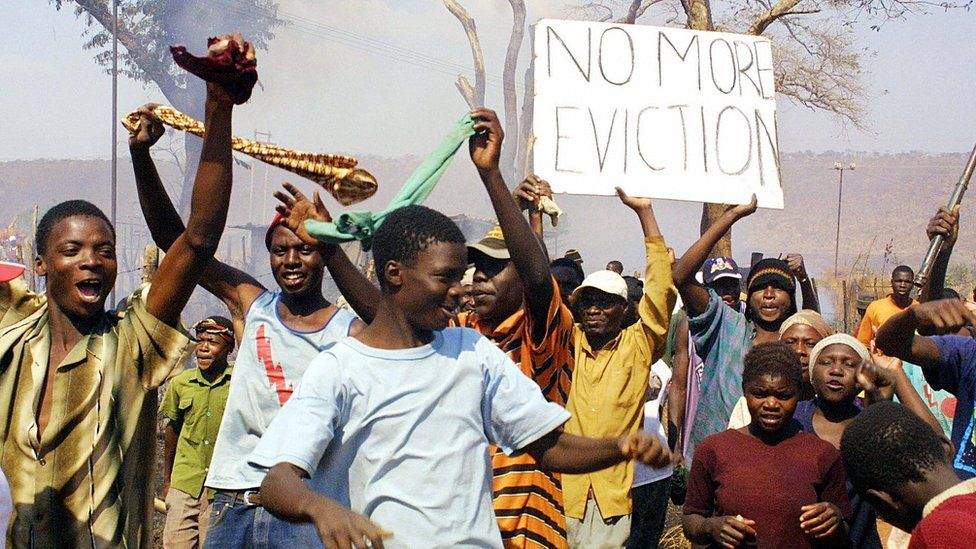 "Residents wave ""no more eviction"" placard in Porta Farm slum, west of Harare, July 2005"