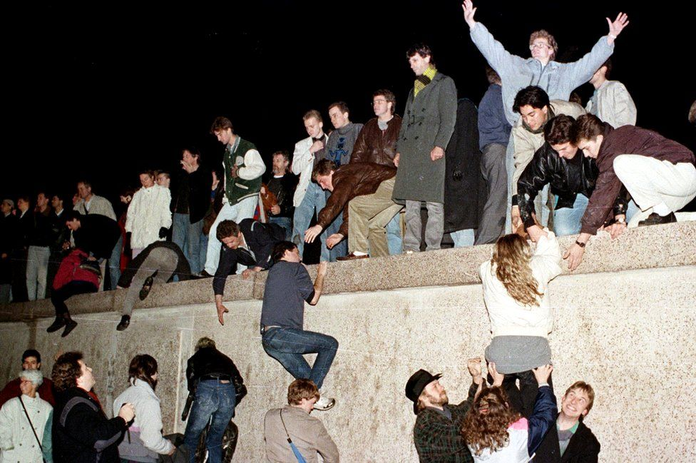 East German citizens climb the Berlin wall at the Brandenburg gate after the opening of the East German border was announced in Berlin on 9 November 1989