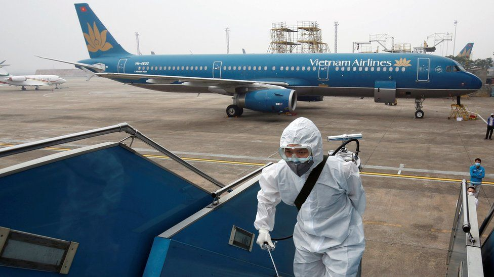Man in protective suit boarding plane