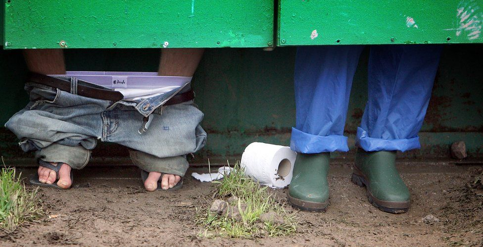 Festival goers (pictured with just their lower legs showing under a toilet door) use the toilets at Glastonbury Festival in Somerset, UK