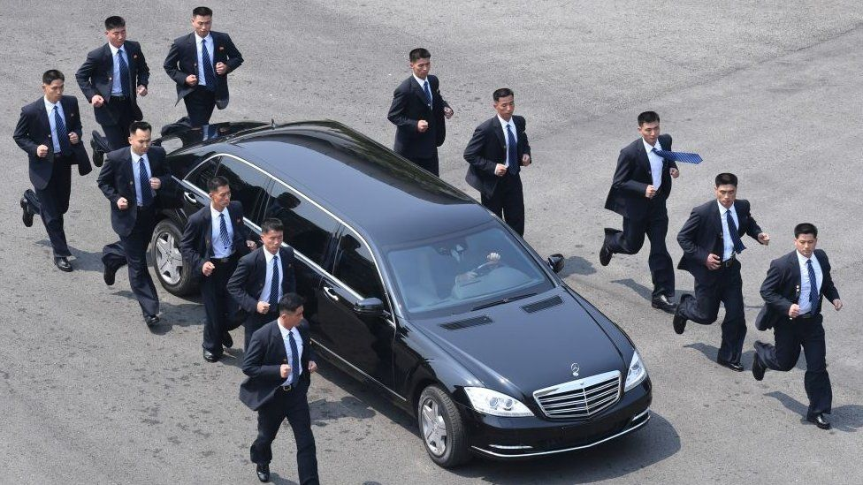 North Korean bodyguards jog next to a car carrying North Korea's leader Kim Jong Un