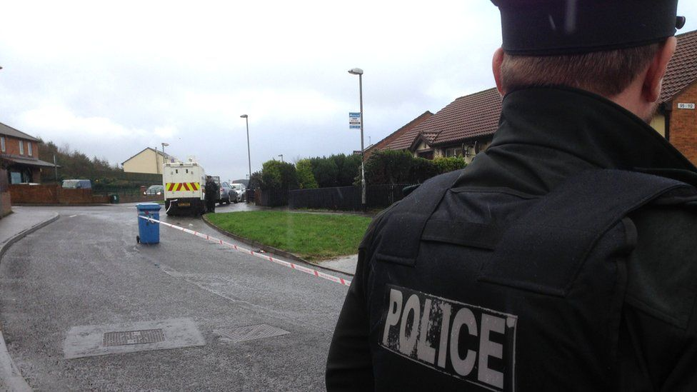 The back of a PSNI officer facing a cordoned off area with a police van visible