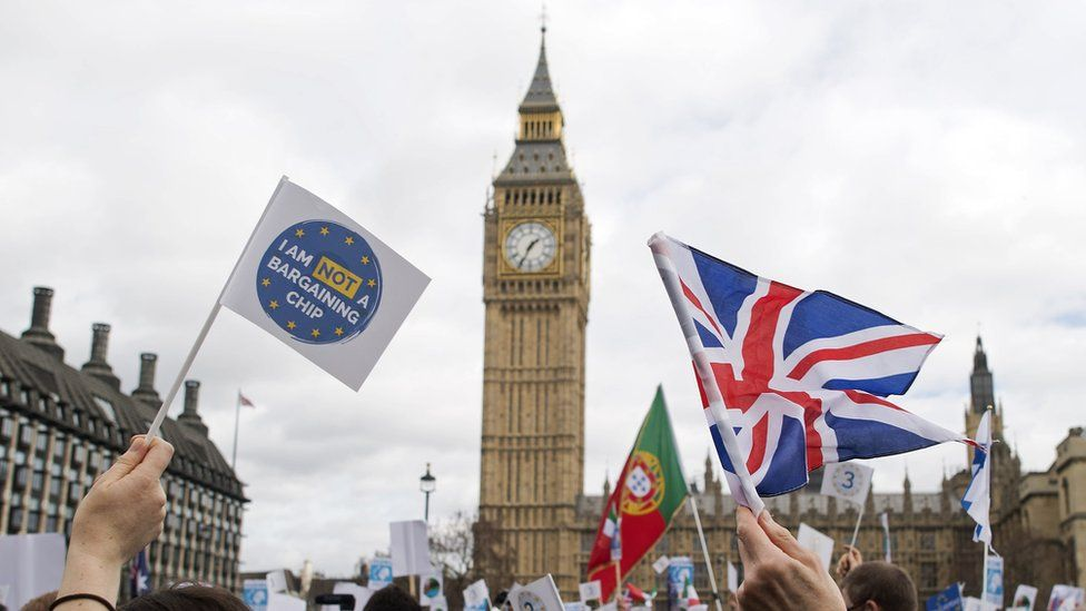 Flags are waved in front of the Elizabeth Tower, better known as 'Big Ben', near the Houses of Parliament during a 'Flag Mob' demonstration in Parliament Square in central London on February 20, 2017, part of a national day of action in support of migrants in the UK
