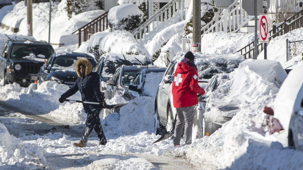 """Residents shovel snow on a street in a neighbourhood of Boston, Massachusetts, a day after the region was hit with a """"bomb cyclone"""", 5 January 2018"""