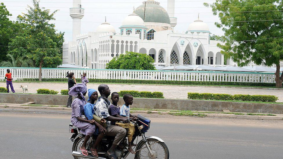 A picture taken on July 28, 2010 shows an Okada, a public transport motorcylist, carrying four passengers driving past a mosque in Maiduguri.