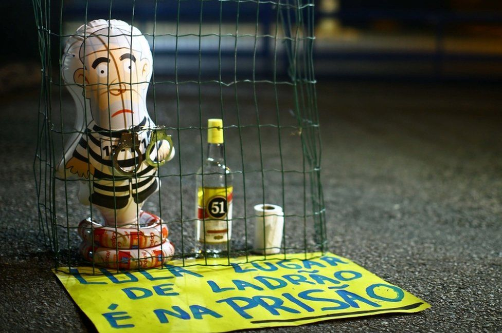 """Pictured: A balloon depicting Lula as an inmate, and a sign reading """"Lula, the place for a thief is prison."""""""