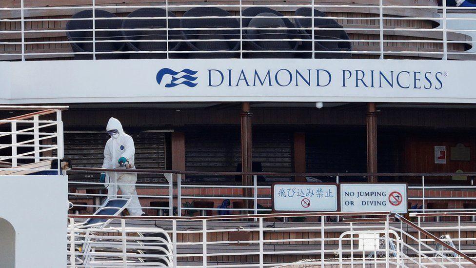 A worker in protective gear is seen on the cruise ship Diamond Princess seen at Daikoku Pier Cruise Terminal in Yokohama, south of Tokyo