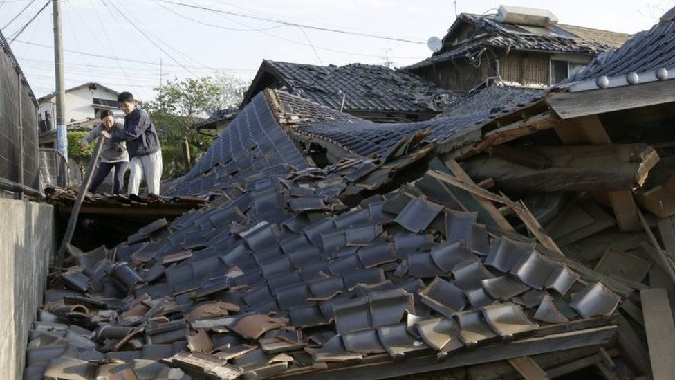 Residents cross over debris of collapsed buildings in Mashiki, south-western Japan. Photo: 16 April 2016