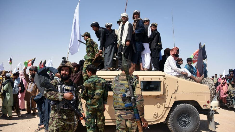 Afghan Taliban militants and residents stand on a armoured Humvee vehicle of the Afghan National Army as they celebrate a ceasefire on the third day of Eid in Maiwand district of Kandahar province