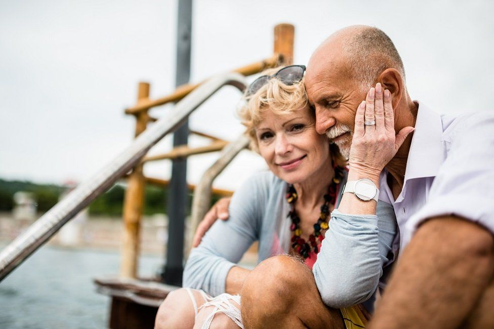 Man and woman sit on dockside