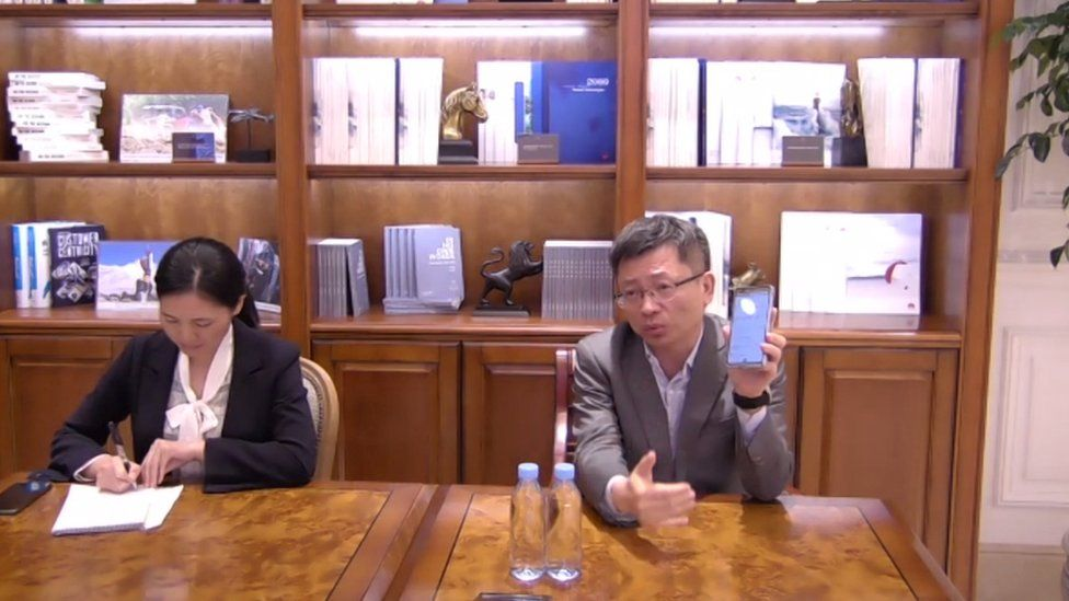 Mr Jiang, right, holds up a phone to the camera during an interview
