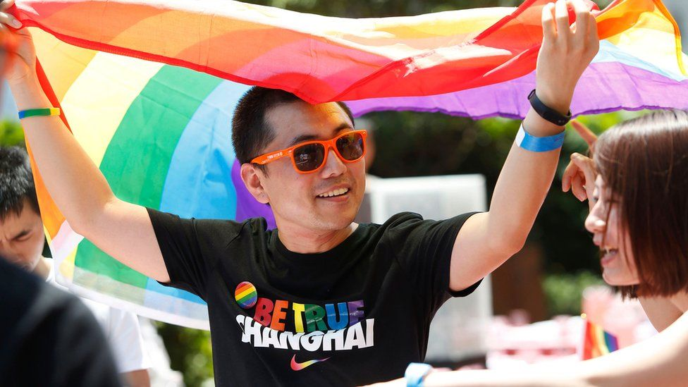 A man holds a rainbow flag after taking part in the Pride Run in Shanghai