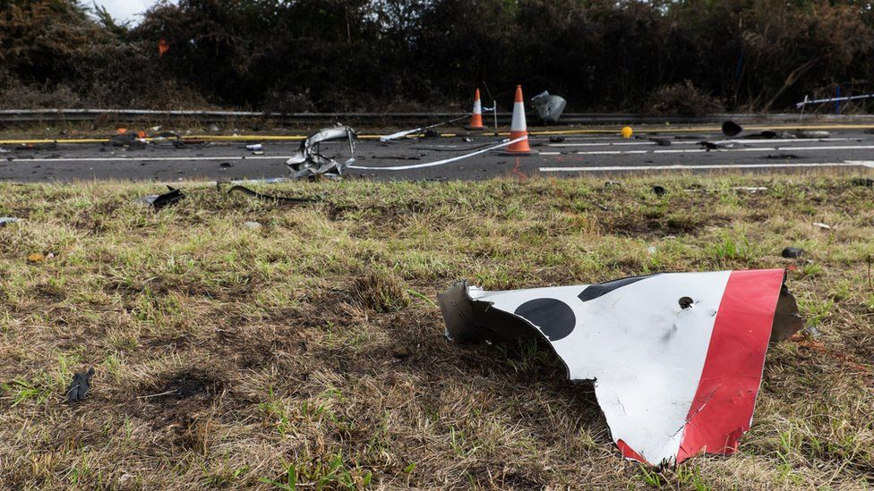 A broken road sign lies near the road where the plane crashed