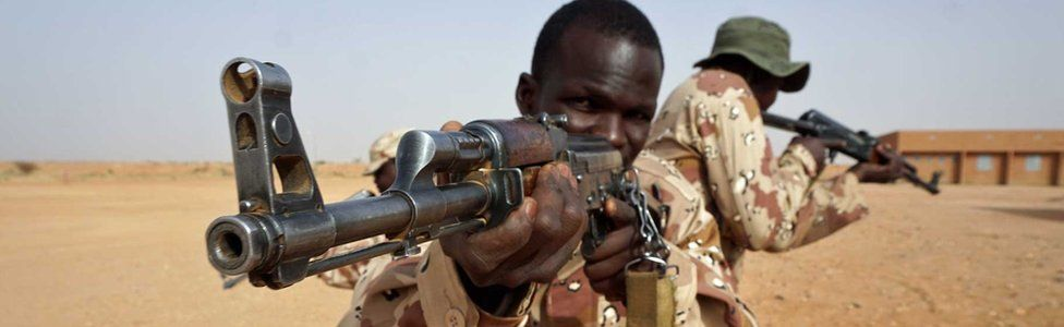 Two African soldiers aim guns in the desert