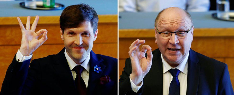 """A composite image shows Martin Helme (L) and Mart Helme make the """"OK"""" hand gesture with thumb and forefinger closed, other fingers extended, in a parliament chamber"""