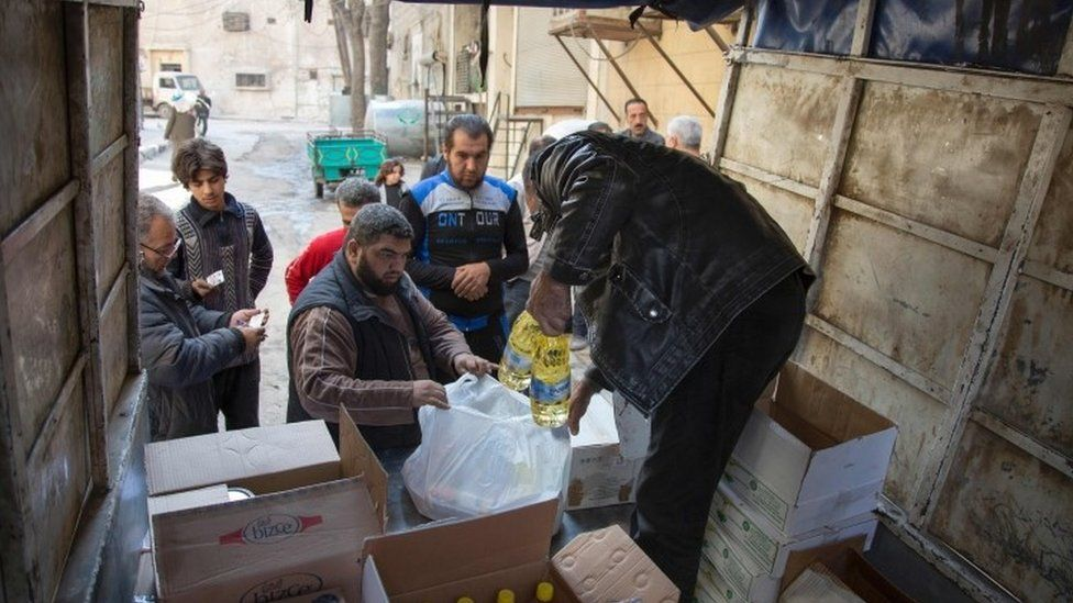 Syrian families receive aid packages by Al-Sham Humanitarian Foundation in the rebel-held neighbourhood of al-Marjah in the northern city of Aleppo (15 November 2016)