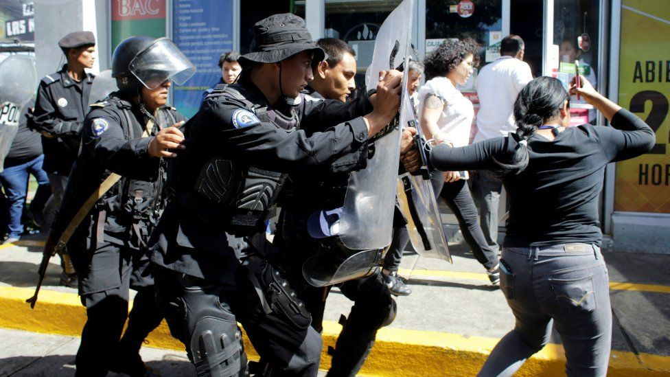 Riot police dislodge journalists from the main entrance to police headquarters in Managua, Nicaragua December 15, 2018