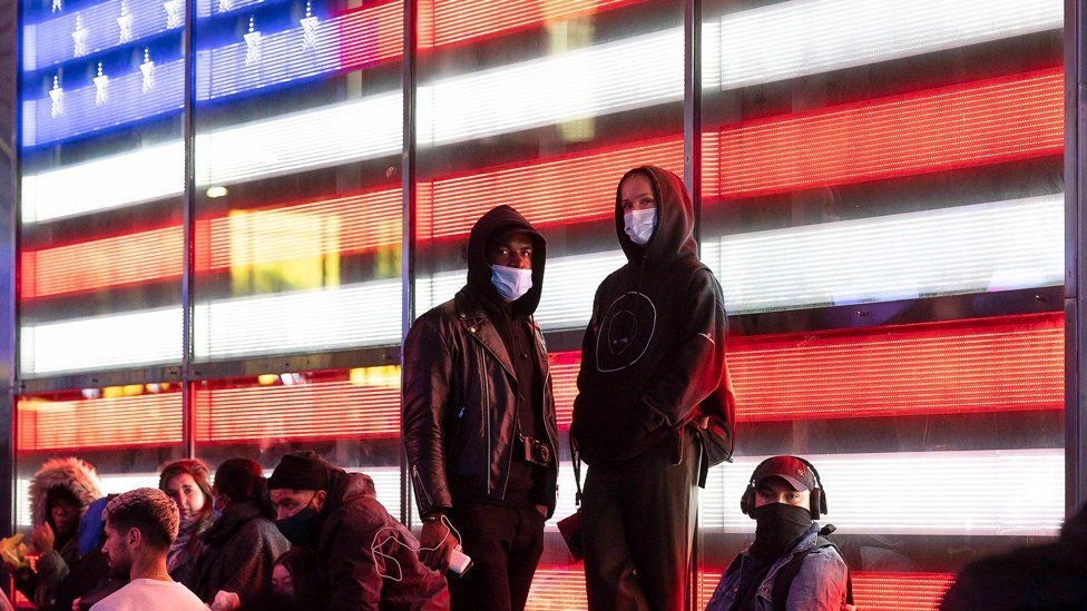 People (wearing masks and hoodies) stand in front of a large screen displaying the US flag in Times Square, New York