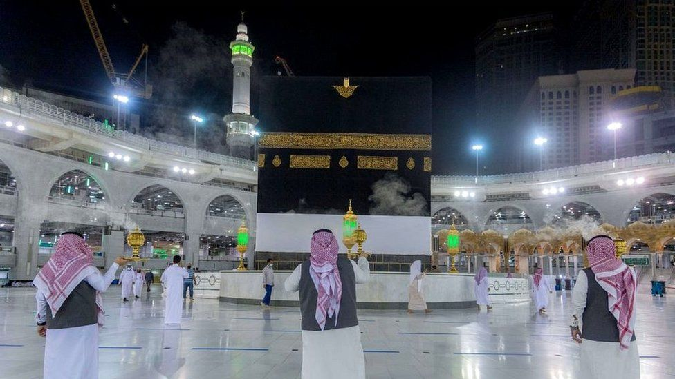 Members of the hajj staff burning incense while a few pilgrims walk round the Kaaba, at the Grand Mosque in the holy city of Mecca, on July 26, 2020