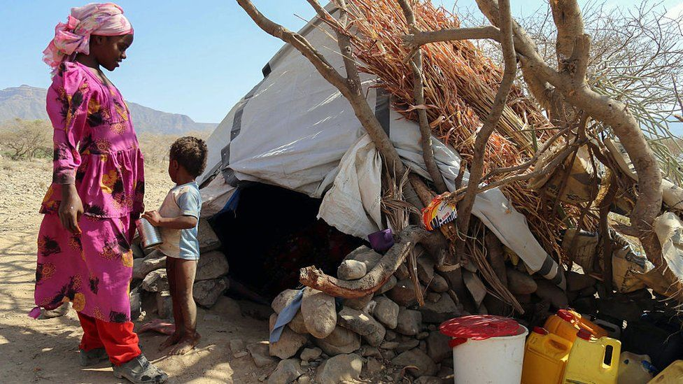 A woman and child stand outside their shelter at a camp for internally displaced people on the outskirts of the southern city of Taiz, Yemen, on 11 January 2017
