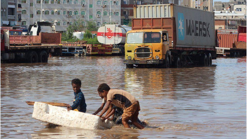 Children push a makeshift raft in a flooded street in Aden (22/04/20)