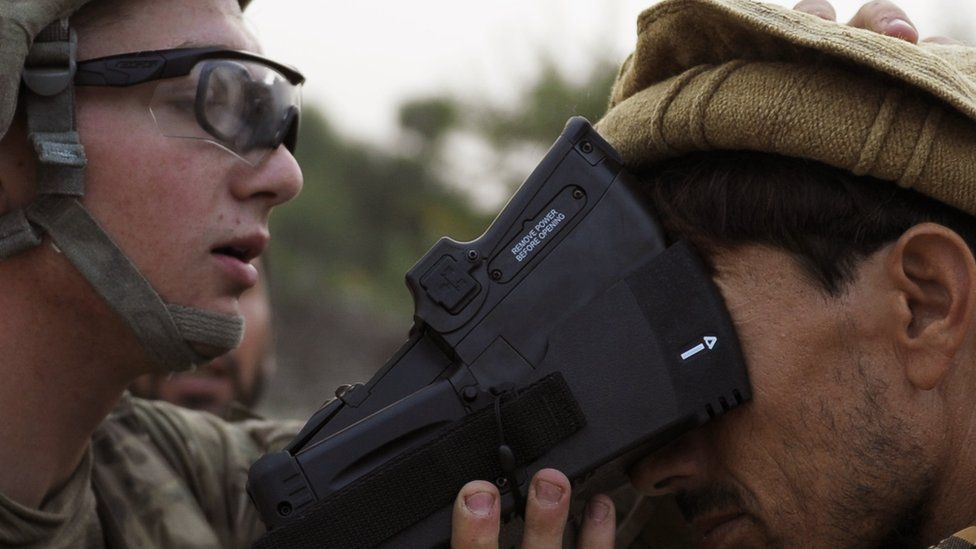 A US solider collects biometric information from a villager