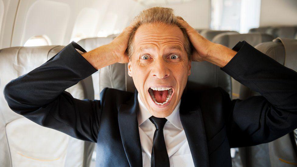 Stressed businessman on plane