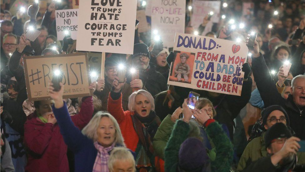 Demonstrators hold placards during a protest in Glasgow against US President Donald Trump's controversial travel ban on refugees and people from seven mainly-Muslim countries