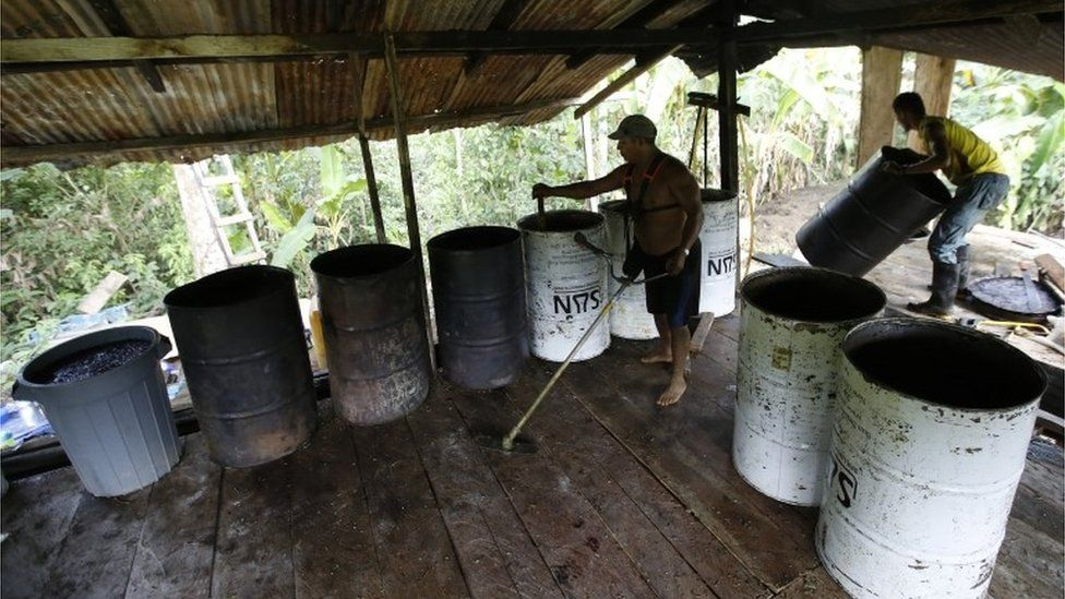 Workers manning barrels with a mix of mulched coca leaves and chemicals as part of the process to make coca base in the southern Colombia (03/03/2017)