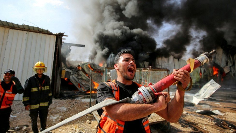 A Palestinian firefighter reacts as he participates in efforts to put out a fire at a sponge factory