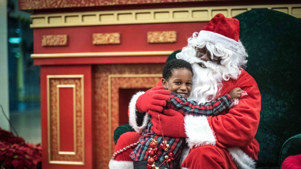 Kenny Green, playing Santa, with Christopher Pettus, at the Shops at Iverson