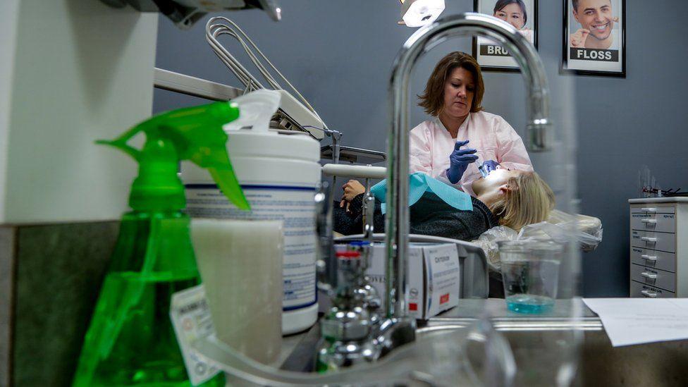Dentist cleans patients teeth