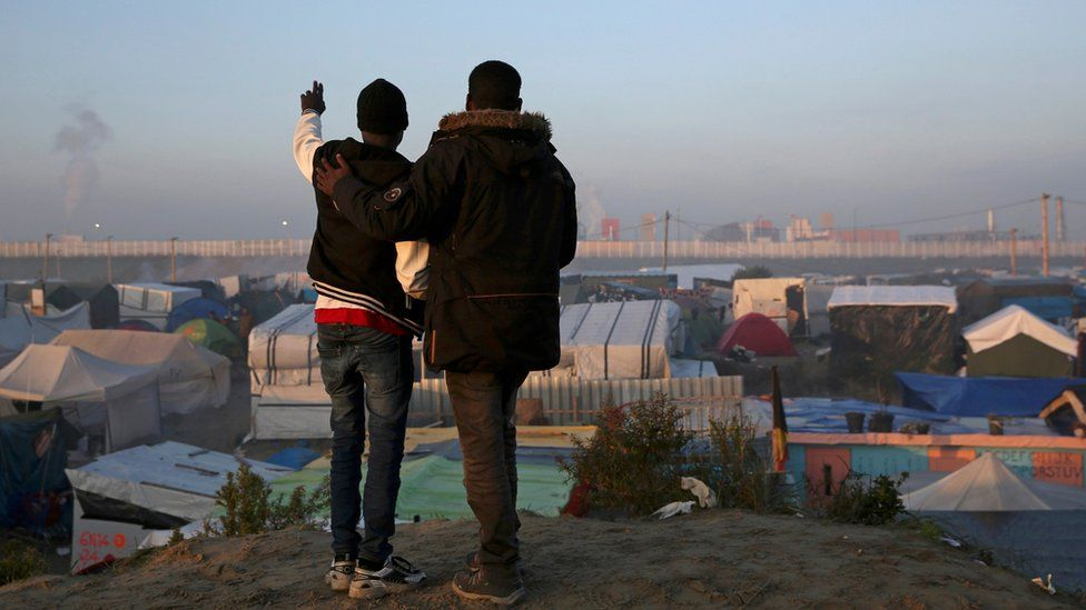 Young migrants watch the camp being demolished in 2016