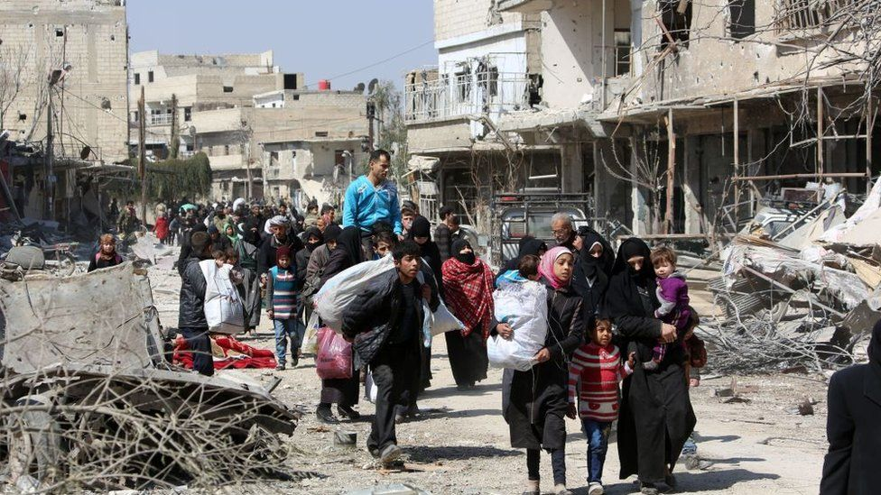 Syrian civilians leave the rebel-held town of Jisreen in the southern Eastern Ghouta during a government offensive (17 March 2018)