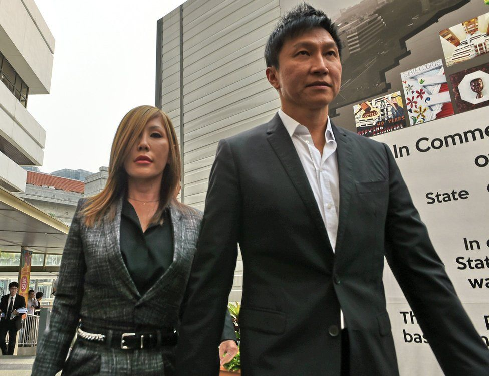 City Harvest Church founder Kong Hee (R) arrives with his pop-singer wife Ho Yeow Sun (L) at the district state courts