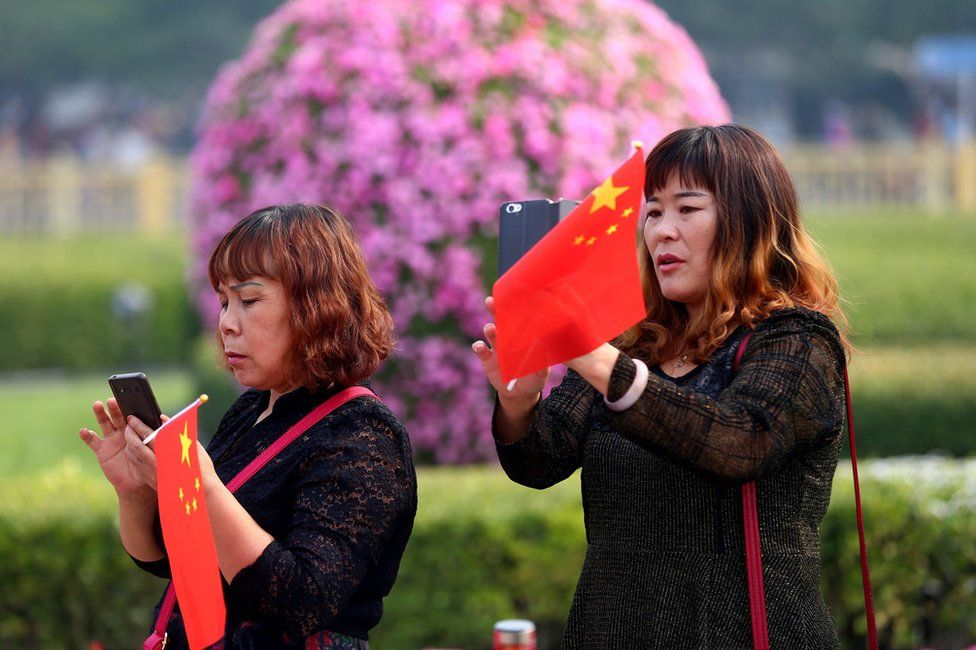 Tourists holding Chinese national flags use mobile phones to take photos at Tiananmen Square during National Day celebrations in Beijing, China, 1 October 2016.