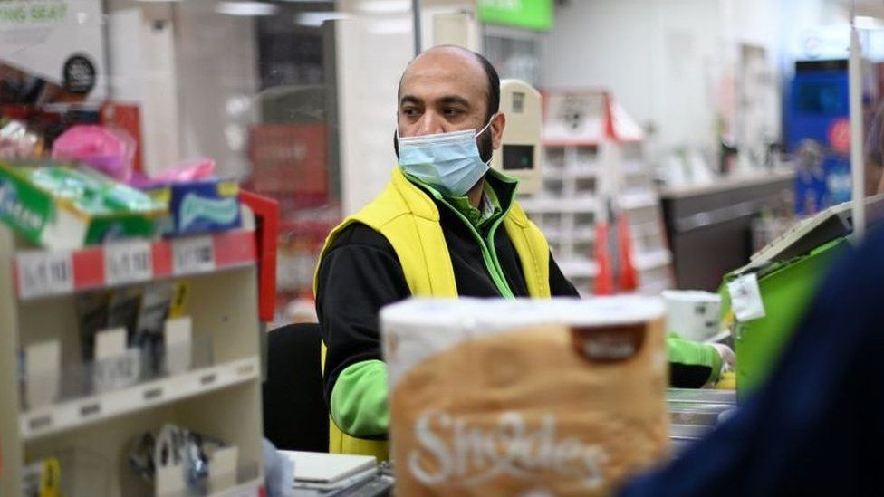 A shop worker wearing a protective face covering to combat the spread of the coronavirus, serves customers at an Asda supermarket in London