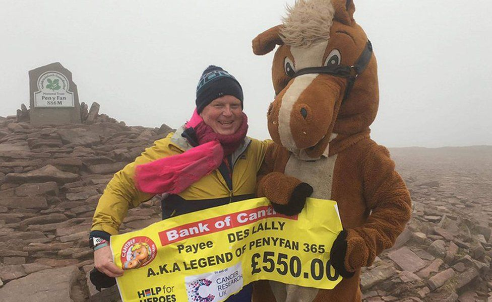 Des at the summit receiving a cheque for £550 from a person dressed up as a horse