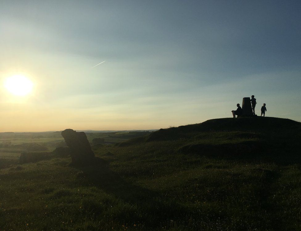 Three figures silhouetted by a sunset