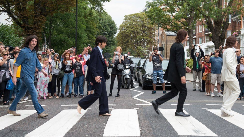 The cast of the West End show Let It Be come together on the zebra crossing outside Abbey Road Studios