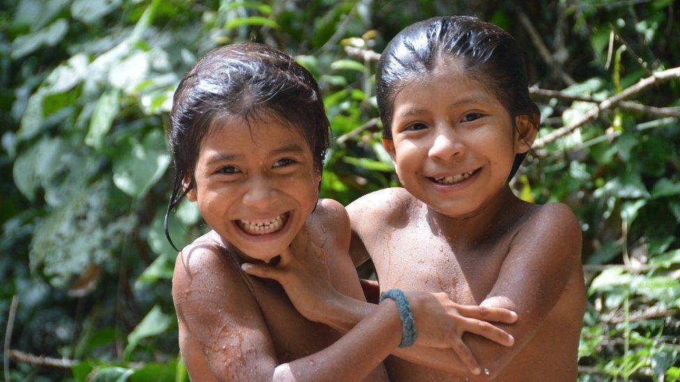 Two Awa children smile for the camera in 2014